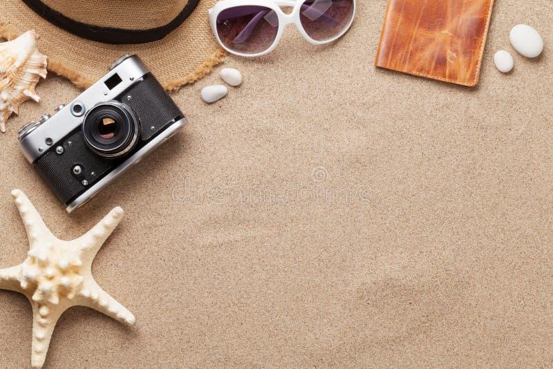 旅行假期与太阳镜、帽子、护照、照相机和海星的背景概念在沙子背景 与拷贝空间的顶视图 免版税库存照片