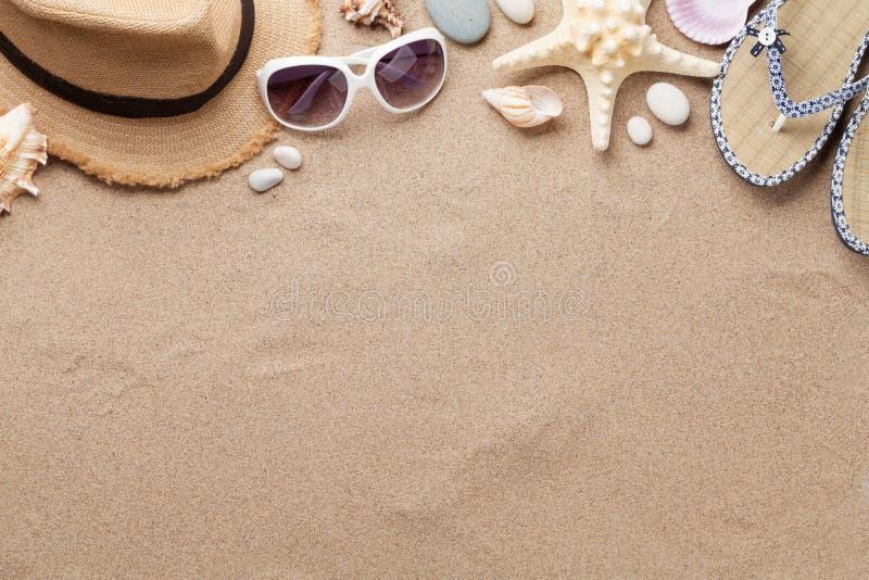 旅行假期与太阳镜、帽子和海星的背景概念在沙子背景 与拷贝空间的顶视图 平的位置 库存照片