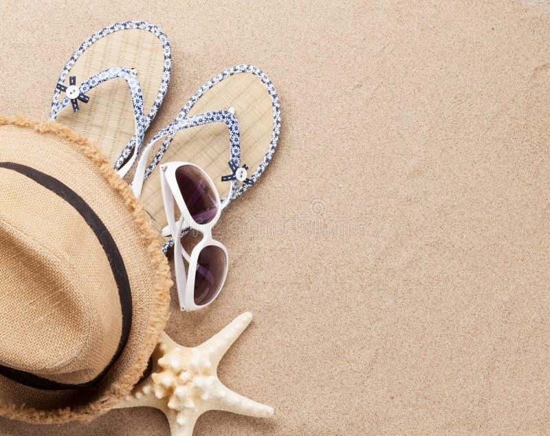 旅行假期与太阳镜、帽子和海星的背景概念在沙子背景 与拷贝空间的顶视图 平的位置 免版税库存照片