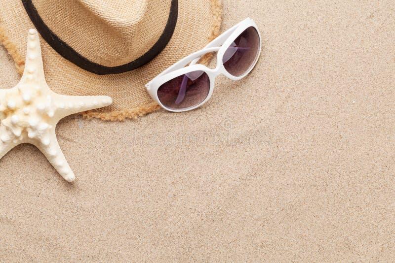 旅行假期与太阳镜、帽子和海星的背景概念在沙子背景 与拷贝空间的顶视图 平的位置 免版税图库摄影