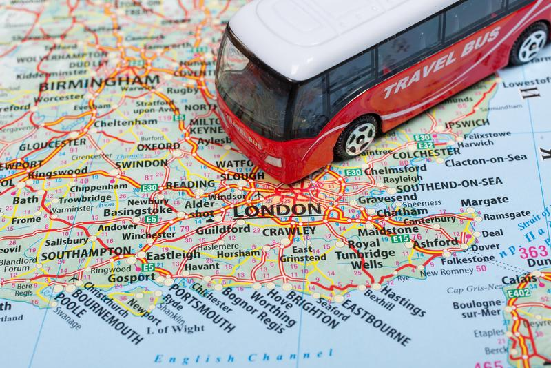 旅行公共汽车模型在伦敦地图的  旅行由公共汽车概念 旅行和旅游业的概念性图象 免版税库存照片