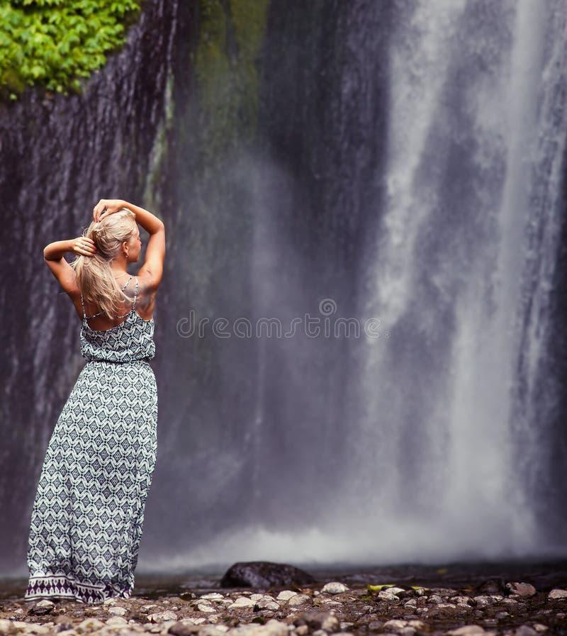 旅行到瀑布的少妇 免版税库存图片