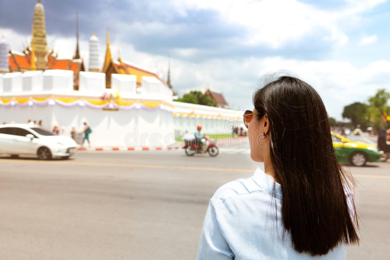旅行到盛大宫殿和Wat Phra Keaw的年轻女人在日落在曼谷,泰国 免版税图库摄影