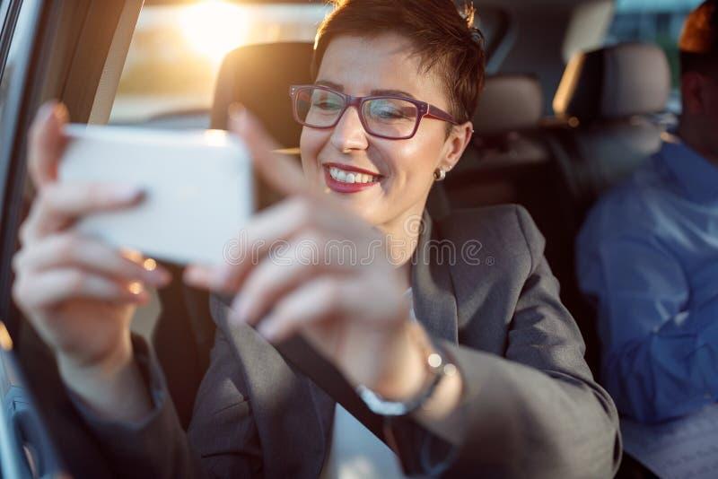 旅行和拍从汽车的女商人照片 库存照片