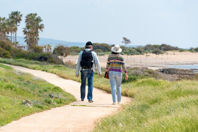 旅行和旅游业 享受看法的成熟家庭夫妇一起走沿海滨,从后面的看法 库存照片