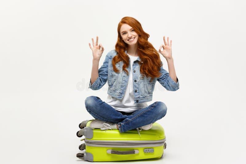 旅行和生活方式概念:坐手提箱和显示好手指标志的年轻白种人妇女 查出在白色 库存图片