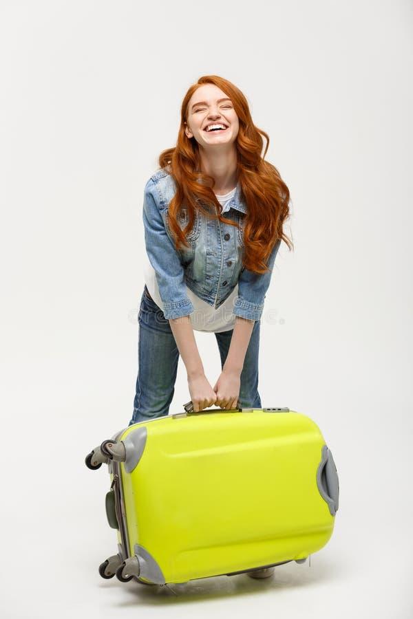 旅行和生活方式概念:拿着在白色背景的年轻愉快的美丽的妇女绿色手提箱 免版税图库摄影