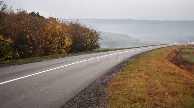 旅行在一个农村秋天风景的柏油路的汽车在日落 免版税库存照片