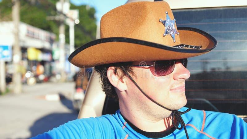 旅行在一辆卡车的帽子和太阳镜的英俊的牛仔在晴天 库存照片