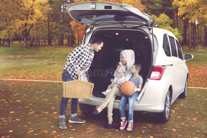 旅行在公园的年轻家庭 免版税图库摄影