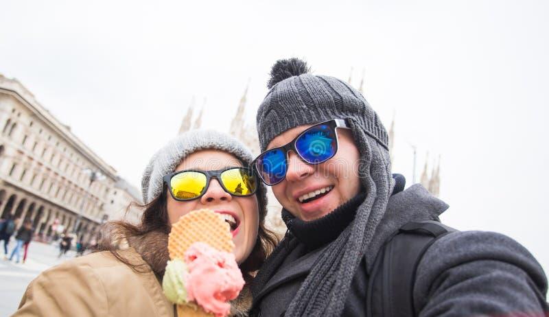 旅行在冬天和意大利概念-愉快的年轻夫妇作为selfie照片用在米兰中央寺院前面的冰淇凌 库存图片