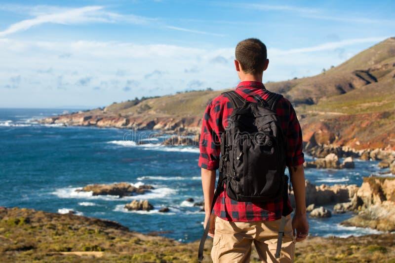 旅行在大瑟尔,有背包的人徒步旅行者享用看法海岸线太平洋,加利福尼亚,美国的 免版税库存图片