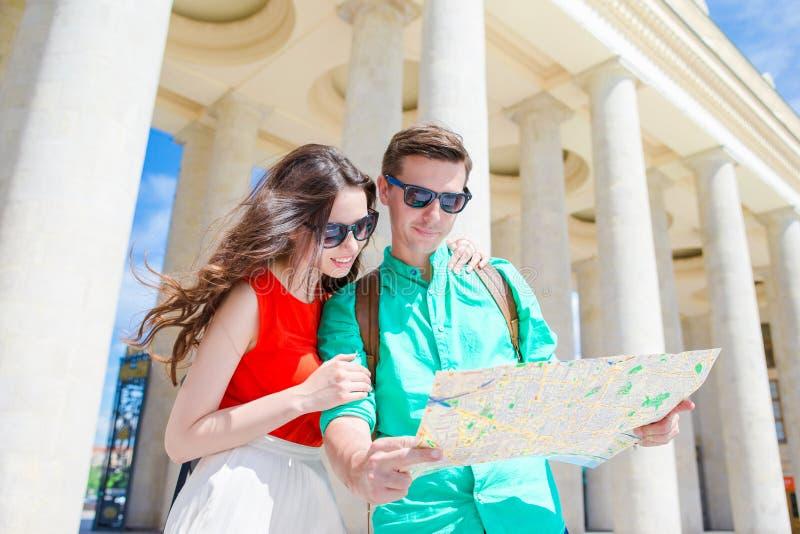 旅行在度假在欧洲微笑的年轻旅游朋友愉快 与城市地图的白种人家庭寻找 库存照片