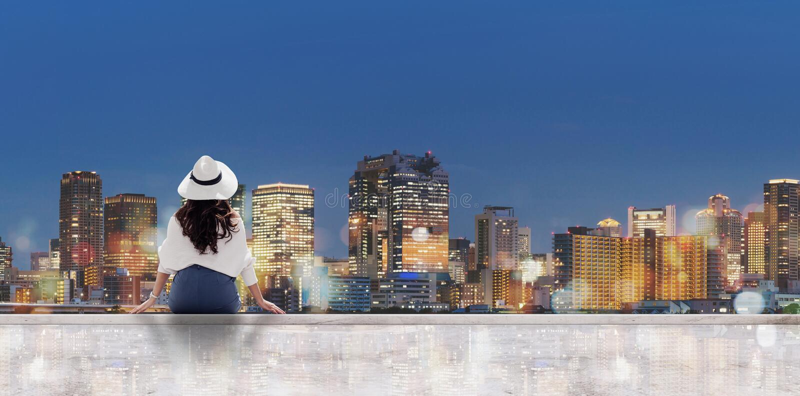 旅行在晚上在城市 白色帽子的年轻女人坐看大阪市的露台在晚上 免版税库存图片