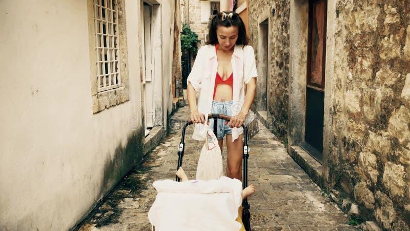 旅行在有一辆婴儿推车的地中海老镇的母亲和婴孩在度假 库存图片