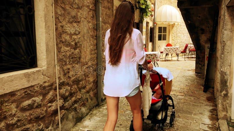 旅行在有一辆婴儿推车的老镇的妈妈和她的婴孩在度假 免版税库存图片