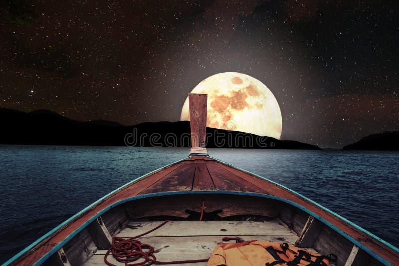 旅行在木小船在与满月和星的晚上在天空 有满月的浪漫和风景全景在海在晚上 库存照片