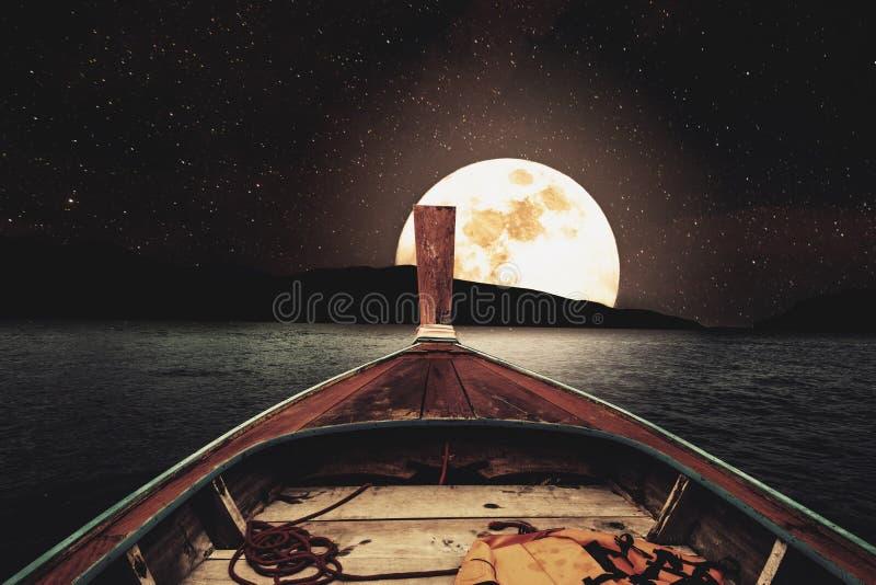 旅行在木小船在与满月和星的晚上在天空 有满月的风景全景在海在晚上,葡萄酒口气 免版税图库摄影