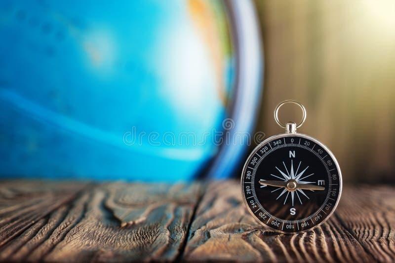 旅行在木背景的指南针和地球globus 旅途,冒险生活方式 家庭路 行程 免版税库存照片
