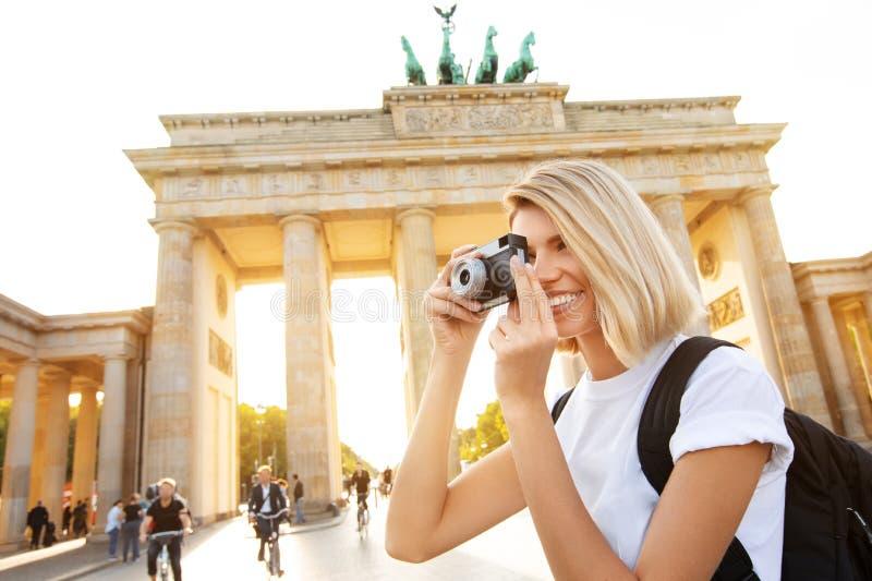 旅行在柏林,有照相机的愉快的旅游妇女在勃兰登堡门,柏林,德国前面 免版税库存图片