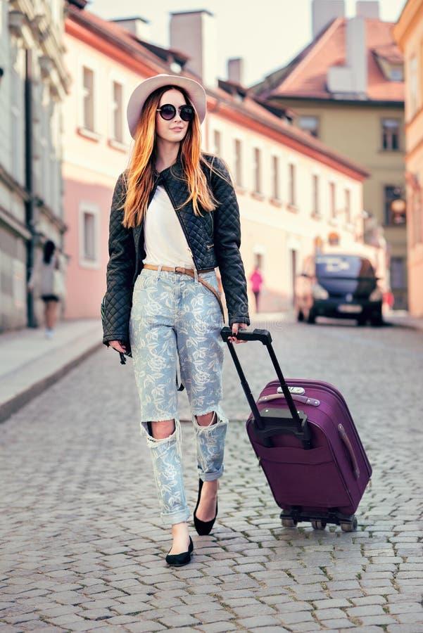 旅行在欧洲和走带着在城市街道上的手提箱的美丽的旅游妇女 人旅行概念照片  免版税库存图片