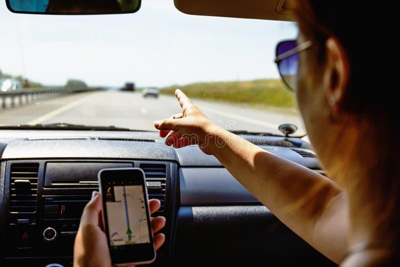 旅行在汽车概念,女孩展示智能手机在她的有被打开的gps航海的app手上 免版税库存照片
