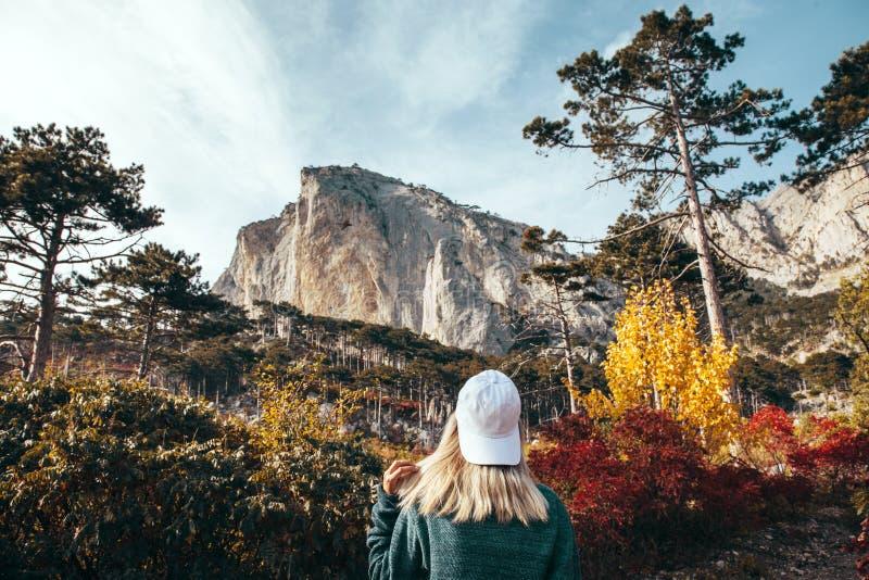 旅行在秋天森林里的女孩由山 库存照片