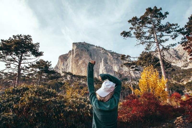 旅行在秋天森林里的女孩由山 库存图片