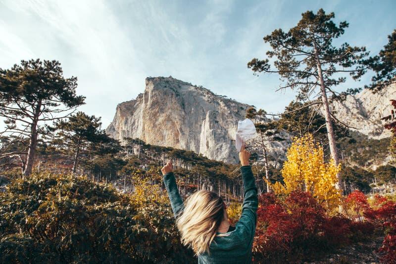旅行在秋天森林里的女孩由山 免版税图库摄影