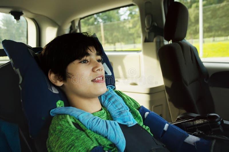 旅行在障碍车的轮椅的年轻残疾男孩 库存照片