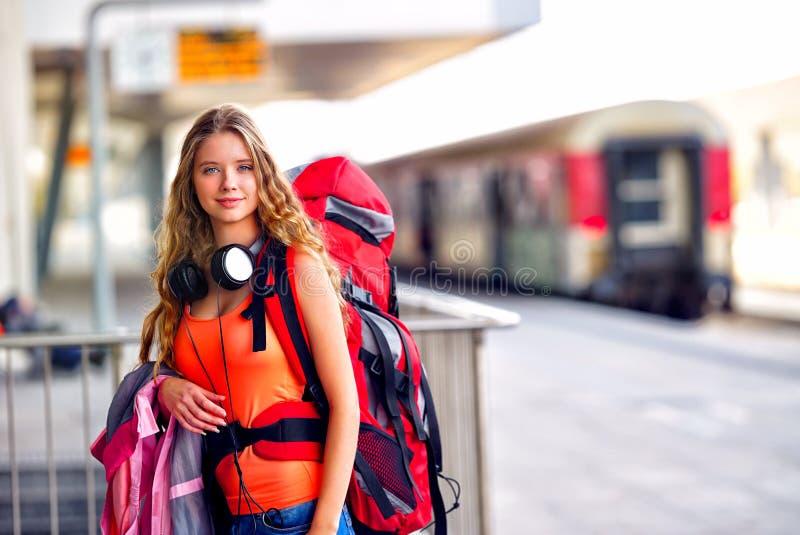 旅行家女孩女性背包和旅游业成套装备在火车站 免版税库存照片