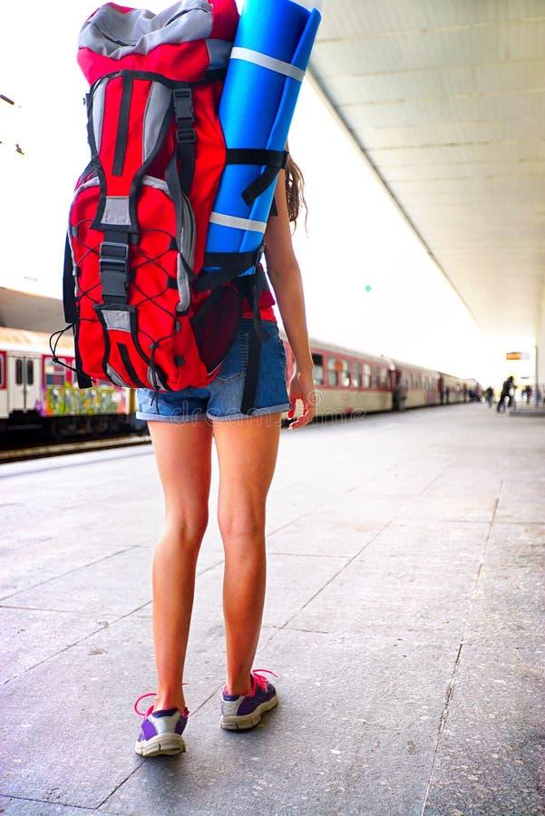 旅行家女孩女性背包和旅游业成套装备在火车站 库存图片