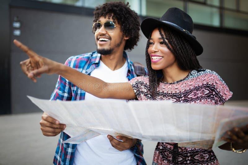 旅行家愉快的年轻黑夫妇在手上的拿着地图 库存照片