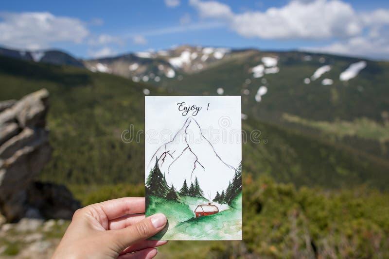 旅行明信片在手上有山背景,在山的冒险,享受片刻 免版税库存图片