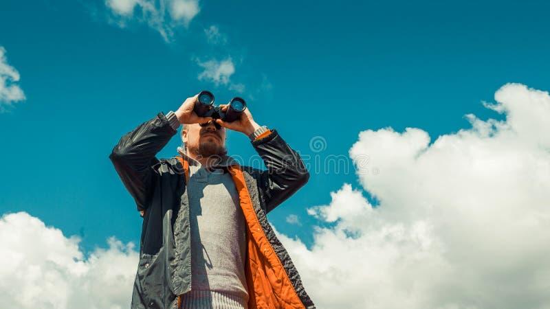 旅行查寻侦察员概念 远足看通过在距离的双筒望远镜的人反对天空 低角度点射击 免版税图库摄影