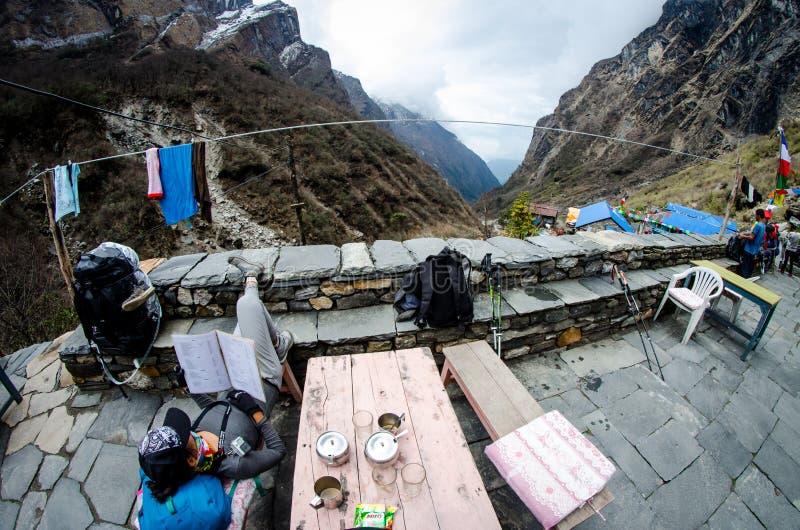 旅行概念,愉快的游人和在安纳布尔纳峰基地凸轮放松 库存图片