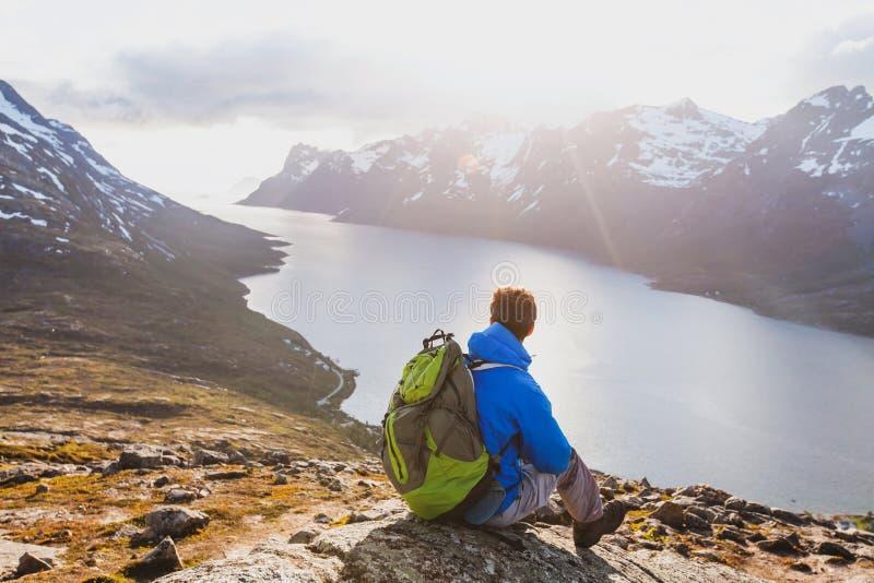 旅行概念,有背包的远足者旅客享受挪威的日落风景的 免版税库存图片