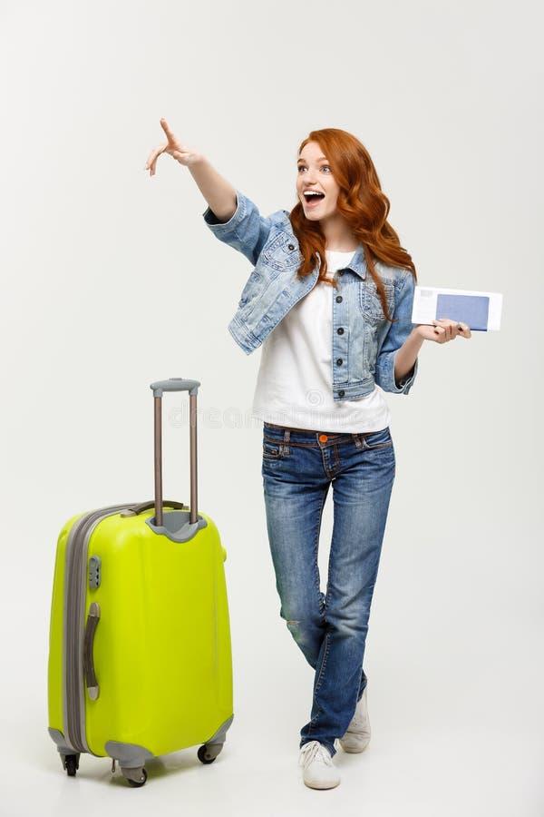 旅行概念:持与飞行票的一件快乐的年轻白种人妇女便服的画象护照,当时 库存图片