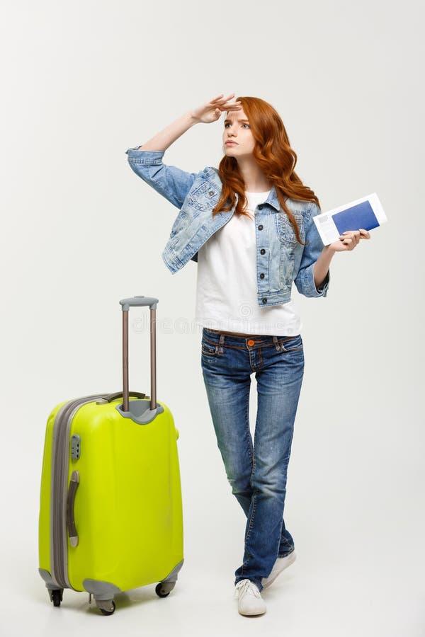 旅行概念:画象少妇坐室外带着等待某人的手提箱看起来生气 免版税库存图片
