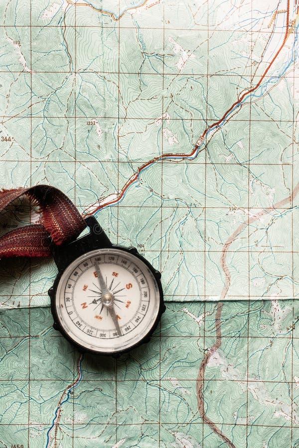 旅行癖和探索概念,说谎在地图,名列前茅vi的老指南针 库存照片
