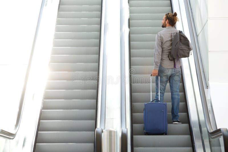 去旅行的人与手提箱和袋子的自动扶梯 免版税库存照片