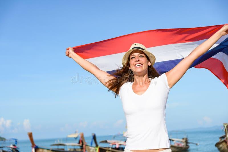 旅行的妇女向获得的泰国与旗子的乐趣 免版税库存照片