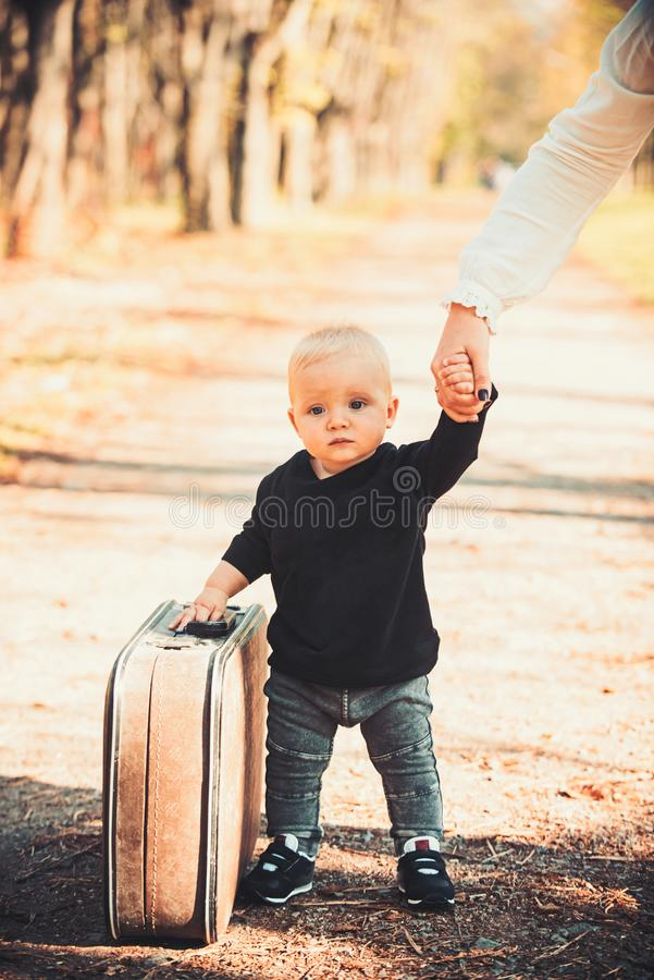 旅行的孩子运载在自然风景的手提箱 与葡萄酒袋子的移动的男婴旅行与母亲递 免版税库存图片