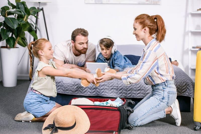 旅行的美丽的愉快的家庭包装行李 库存图片
