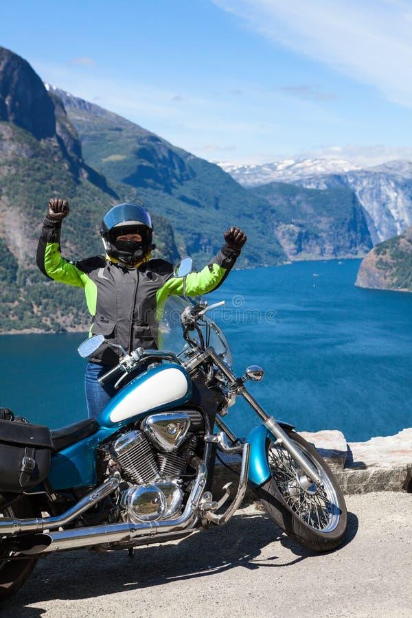 旅行的退出的妇女摩托车骑士glads乘摩托车在挪威,斯堪的那维亚 与北海和海湾的观点 图库摄影