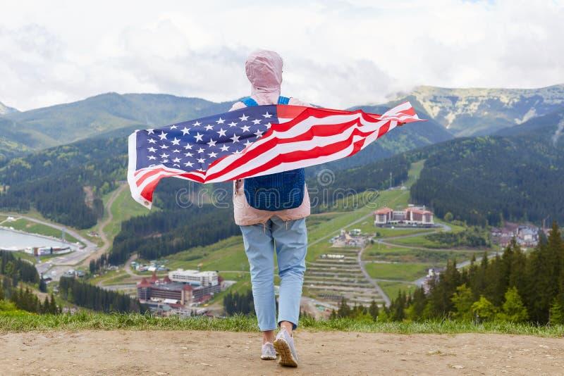 旅行身分后面看法在拿着在她的后面,佩带的牛仔裤,运动鞋和玫瑰色夹克的小山顶部的美国旗子,摆在  库存图片