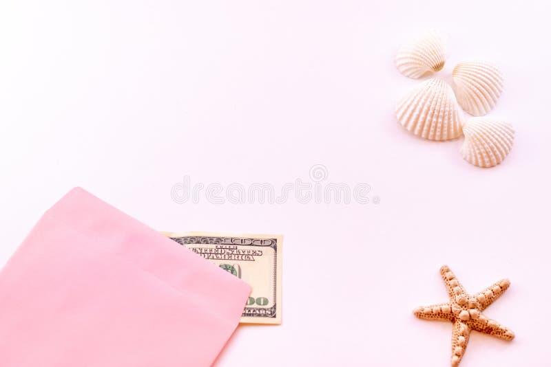 旅行预算 海星、贝壳和金钱在一个桃红色信封在桃红色背景 库存照片