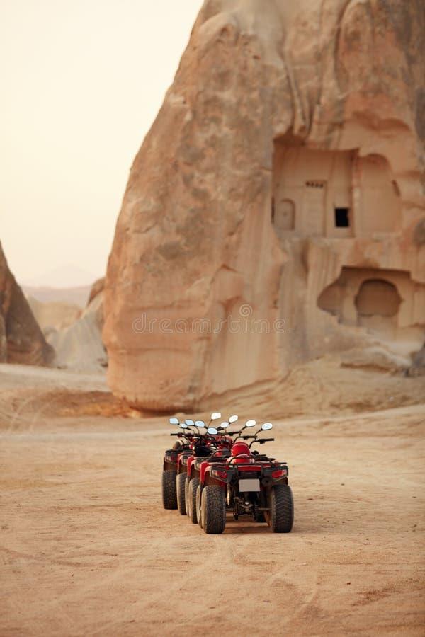 旅行 红色方形字体在沙漠,ATV车骑自行车站立在沙子 免版税库存照片