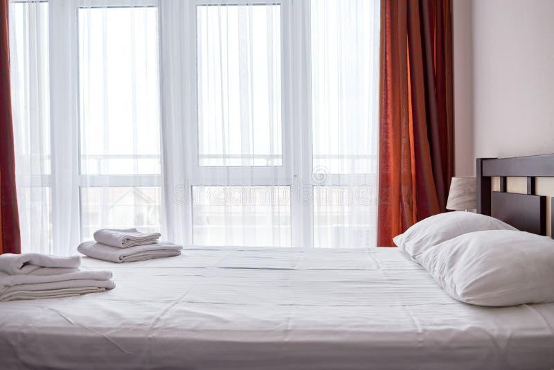 旅馆与空的双人床的卧室内部与木床头板和大窗口,拷贝空间 白色板料,软的枕头 免版税库存图片