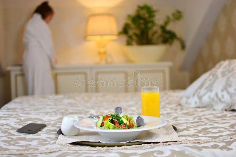 旅馆在一张舒适的床上的早餐沙拉与背景的一个女孩 库存图片
